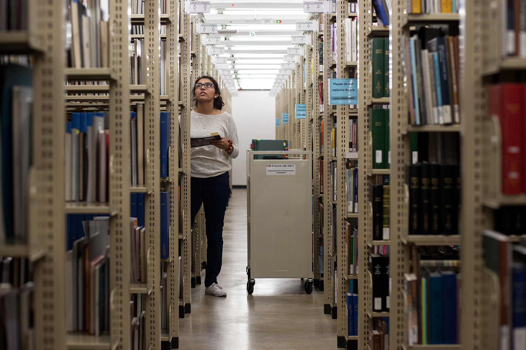 Student in the stacks at the Benson Latin American Collection.