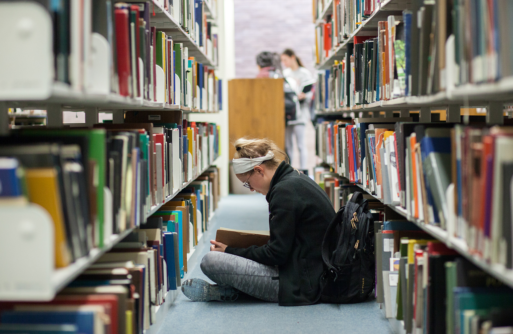 Student in the 5th floor stacks at the Fine Arts Library.