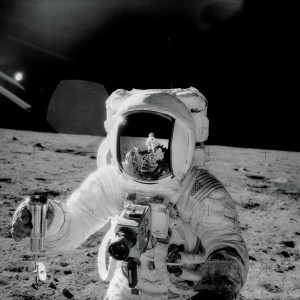 "Apollo 12 astronaut Alan Bean holds a special environmental sample container which holds soil collected during the second moonwalk EVA. Commander Charles ""Pete"" Conrad had just put a soil sample in the tube with a shovel. The picture was taken in the vicinity of Sharp Crater. Conrad took the photograph and can be seen in the reflection in Bean's visor. (Apollo 12, AS12-H-49-7278)."