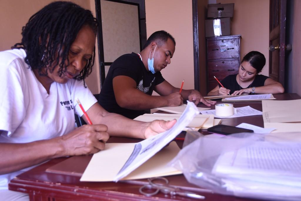 Marta, coordinadora del proyecto digital de PCN, trabaja en la identificación de documentos con dos estudiantes universitarios, Javier y María José (foto: Anthony Dest)