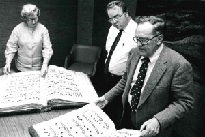Harold Billings looking over a large manuscript of sheet music.
