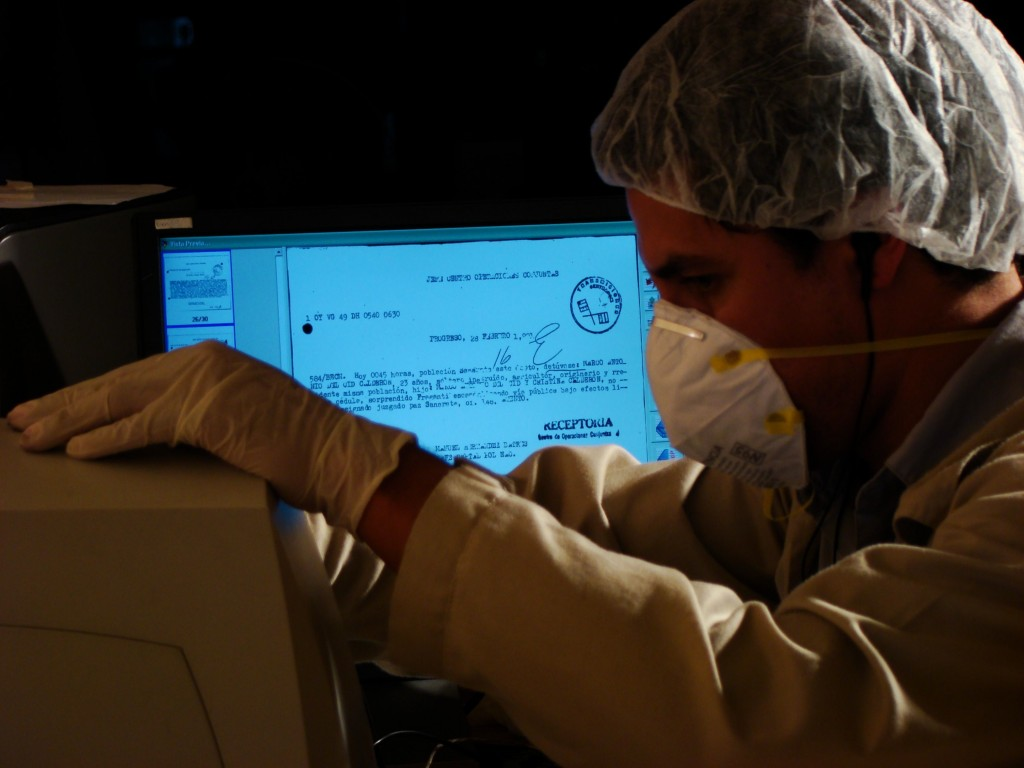 A scanned document appears on the screen as part of the digitization process. Photo courtesy Archivo Histórico de la Policía Nacional, Guatemala.
