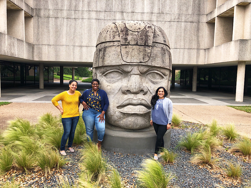 Three people standing with a large Olmec head sculpture.