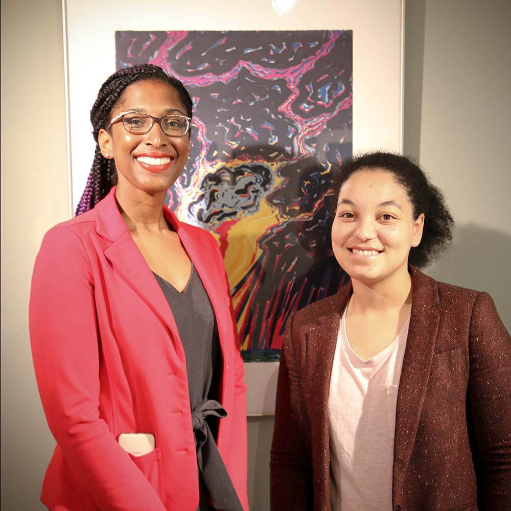 Rachel Winston and Natalie Hill standing in front of a work of art.