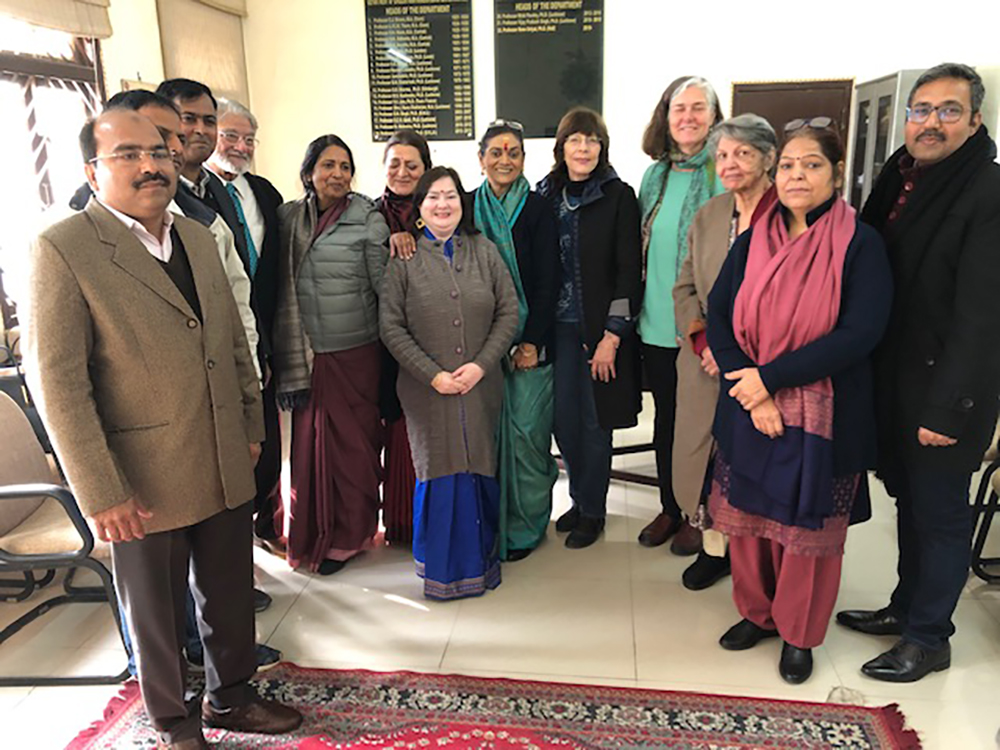 twelve people (from the english department at the university of lucknow and librarian mary rader) standing, smiling for the camera.
