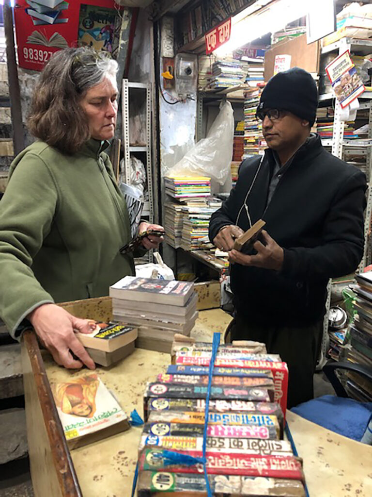 woman in sales transaction with man in black coat and hat, in a book stall