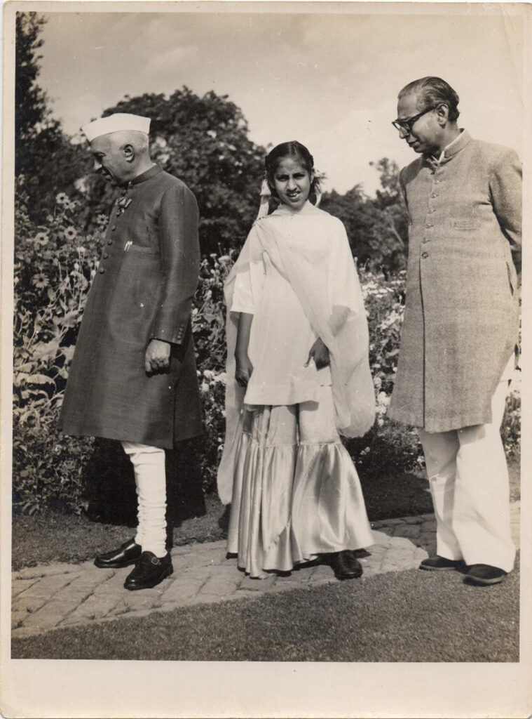 archival photo of three people (Sajjad Zaheer, Jawaharlal Nehru and Nehru's daughter) on a stone pathway in a garden