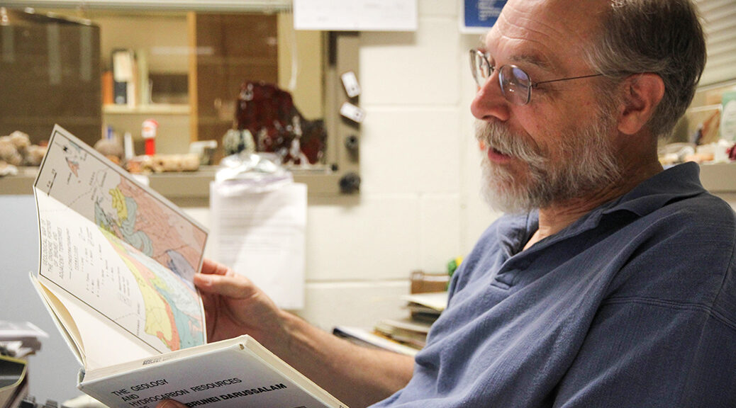 dennis trombatore. bearded man in glasses looking at a geology text.