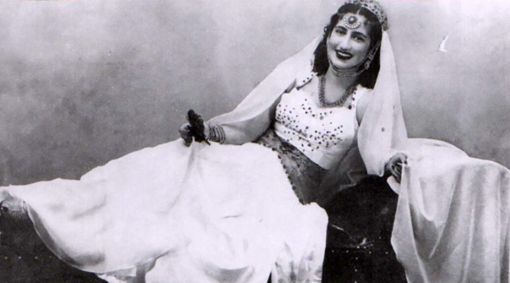 black and white photo of woman with dark hair in white dress reclining on a divan