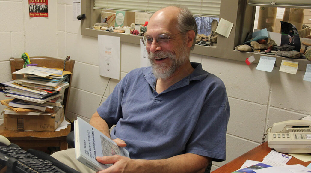 man (dennis trombatore) smile while sitting at desk with geosciences book