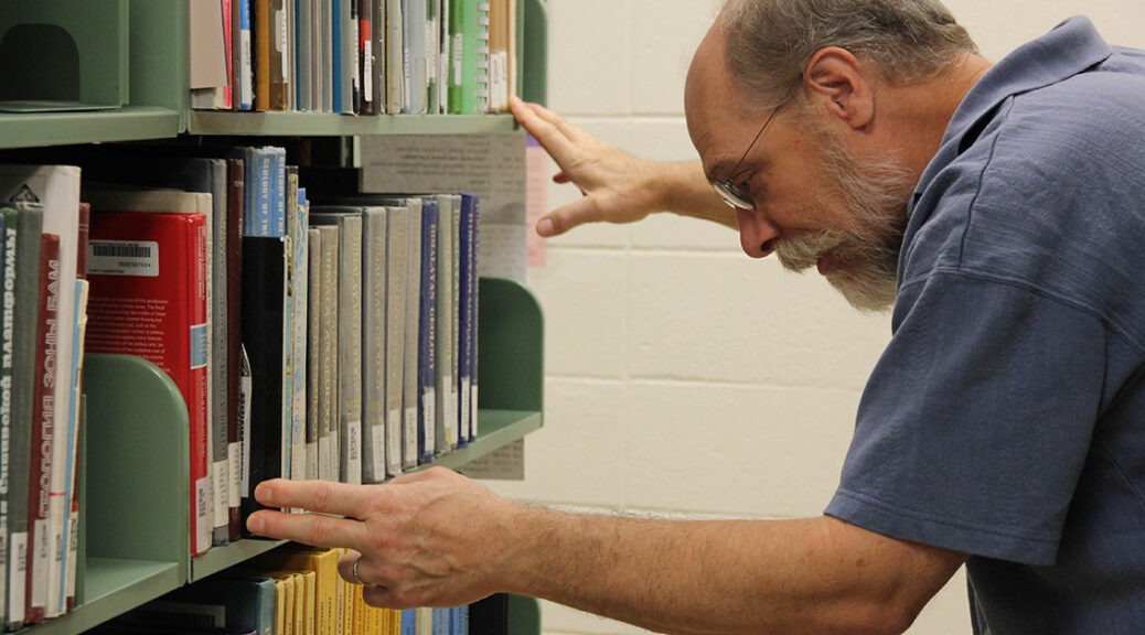 Bearded man in glasses hunched over looking at library books on a shelf.