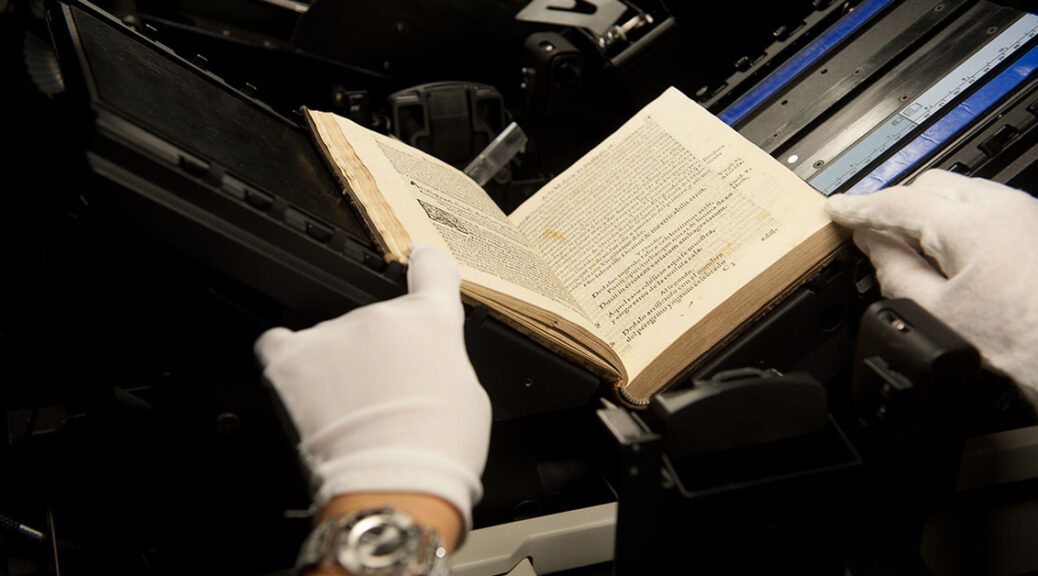 hands in archival protective white gloves holding book in place on flatbed scanner
