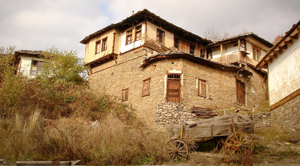 stone house on a hill in Leshten Bulgaria, wagon in front